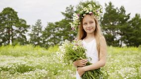 Smiling girl in floral wreath with chamomile bouquet summer field. Portrait girl teenager with flower bouquet posing on. Camomile field at summer day stock video