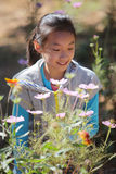 Smiling girl with flowers. In gardens Stock Images