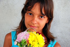 Smiling girl with flowers. Smiling teen girl in blue t-shirt with flowers gift Stock Image