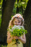 Smiling girl with flowers. Beautiful little blond girl holding bunch of white flowers Royalty Free Stock Images