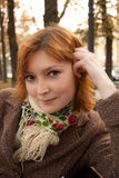 Smiling girl with flowery scarf in autumn park Stock Photos