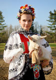 The smiling girl in folk costume with little lamb Stock Images