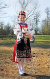 The smiling girl in folk costume with little lamb Stock Photo