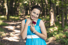 The smiling girl in a forest with red rose in her hand Stock Photo