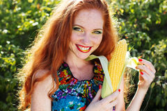 Smiling girl with freckles holding corn cob Royalty Free Stock Photo