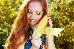 Smiling girl with freckles holding corn cob Stock Photos
