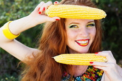 Smiling girl with freckles holding corn cob Royalty Free Stock Image