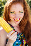 Smiling girl with freckles holding corn cob Stock Image