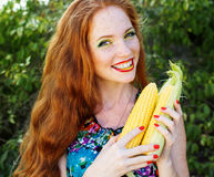 Smiling girl with freckles holding corn cob Royalty Free Stock Photography