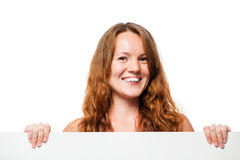 Smiling girl with freckles holding a poster on a white stock photography