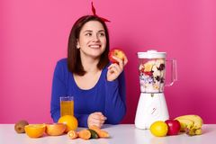 Smiling girl with fresh fruits on table isolated over pink background. Lady looks aside while making coktail. Woman holds apple in royalty free stock photos