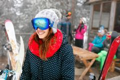 Smiling girl and friends spend winter holidays at mountain cotta. Ge Stock Photography