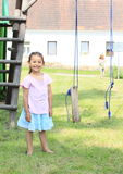 Smiling girl in front of broken swing Royalty Free Stock Photos
