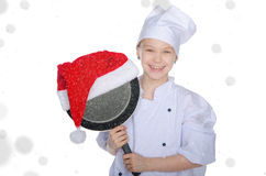 Smiling girl, frying pan and Santa hat with snow Royalty Free Stock Image