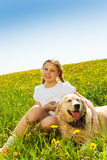 Smiling girl and funny dog sitting on grass Stock Photos