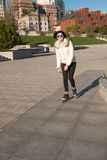 Smiling girl in a funny sunglasses roller skating in the park Royalty Free Stock Photos