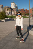 Smiling girl in a funny sunglasses roller skating and posing in Royalty Free Stock Photos