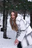 Smiling girl in a fur in the winter forest un Royalty Free Stock Image
