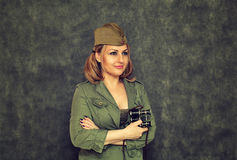 A smiling girl in garrison cap with military binoculars since the Second World War Royalty Free Stock Photography