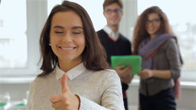 Smiling girl gestures good quality in front of man and woman with tablet