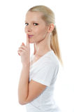Smiling girl gesturing silence. Side view of pretty smiling girl with finger on her lips against white background Stock Image