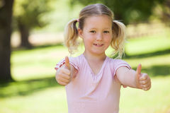 Smiling girl gesturing thumbs up at park. Portrait of a smiling young girl gesturing thumbs up at the park Stock Photography