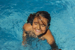 Smiling girl getting out of the water in the pool. stock photos