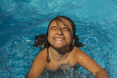 Smiling girl getting out of the water in the pool. royalty free stock image