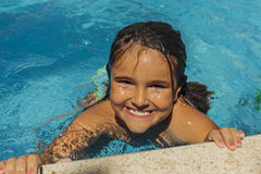 Smiling girl getting out of the water in the pool. royalty free stock images