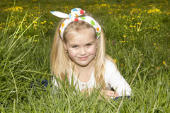 Smiling girl on a glade among flowers Stock Photo