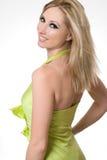 Smiling girl glances over shoulder. Smiling confident female wearing a lime green halter dress glances over her shoulder Royalty Free Stock Photo