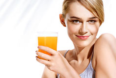 Smiling girl with glass of orange juice on white background. Stock Image