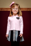 Smiling Girl with Glasses and Bow. A cute little girl with glasses stands very straight and tall with a big, cheesy smile on her face. She looks proud of herself Royalty Free Stock Images