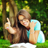 Smiling girl in glasses lying in the park reading a book and sho Stock Photos