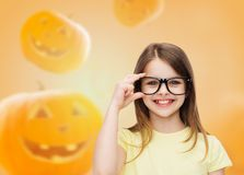 Smiling girl in glasses over pumpkins background Stock Images
