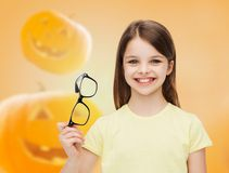 Smiling girl in glasses over pumpkins background Stock Photo