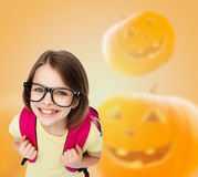 Smiling girl in glasses over pumpkins background Royalty Free Stock Photography