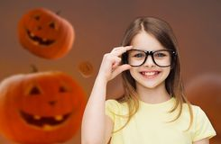 Smiling girl in glasses over pumpkins background Royalty Free Stock Images