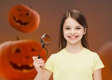 Smiling girl in glasses over pumpkins background Stock Image
