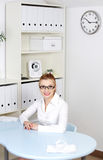 Smiling girl in glasses sitting behind the desk. Royalty Free Stock Images