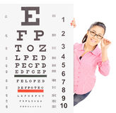 Smiling girl with glasses standing behind eyesight test. Isolated on white background, shot with tilt and shift Royalty Free Stock Images