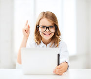 Smiling girl in glasses with tablet pc at school Stock Photography