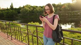 Smiling girl in glasses using smartphone standing outdoors on the bridge. Trendy hipster browsing internet on a phone, texting and communicating stock video footage