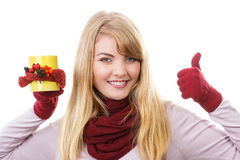 Smiling girl in gloves holding decorated cup of tea and showing thumbs up, autumn decoration stock image