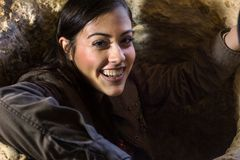 Smiling girl going out of a hole inside a cave Stock Images