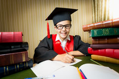 Smiling girl in graduation cap sitting at table between pile of Royalty Free Stock Photos