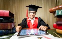 Smiling girl in graduation cap using digital tablet at library Royalty Free Stock Photos