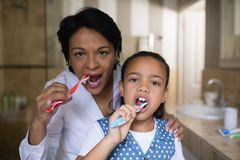 Smiling girl and grandmother brushing teeth in bathroom. Portrait of smiling girl and grandmother brushing teeth in bathroom Stock Photos