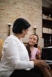 Smiling girl with grandmother holding laptop at home. Smiling girl with grandmother holding laptop while sitting on sofa at home Royalty Free Stock Image