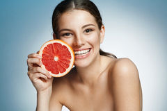 Smiling girl with grapefruit cut in half fruit in hand, with pomelo slice, natural organic raw fresh food concept Royalty Free Stock Photography
